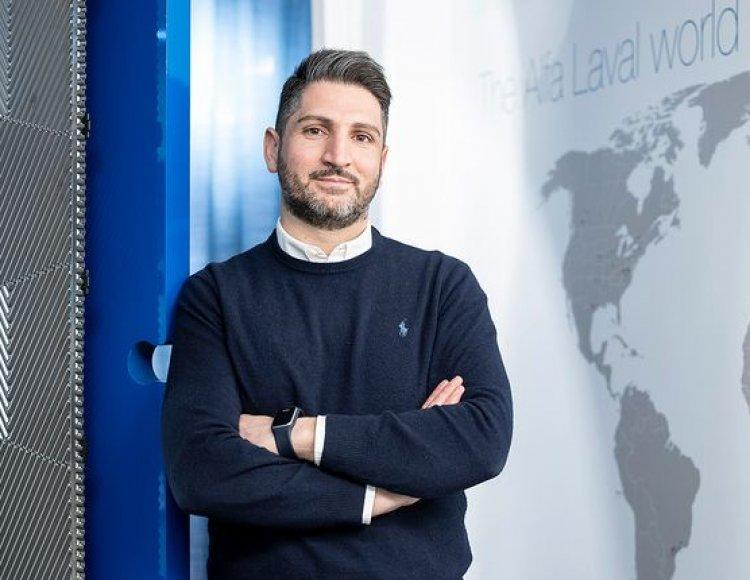 Senan Rasoul ståendes i svart stickad tröja med vit skjorta. I bakgrunden syns en världskarta och en mörkblå gardin.