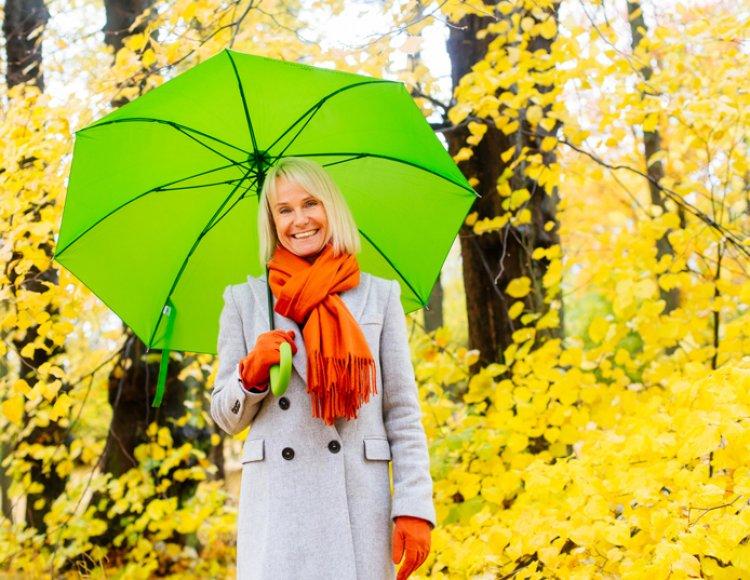 Paulina Ekwall står utomhus med ett grönt paraply och gula höstträd i bakgrunden.