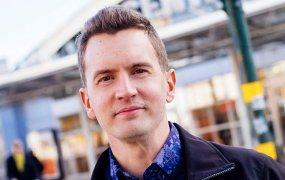 Emil Hammarström ståendes utomhus framför en byggarbetsplats, klädd i blå skjorta och svart jacka.