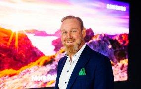 Thomas Holmberg står på Samsungs kontor framför en färgglad tv-skärm.