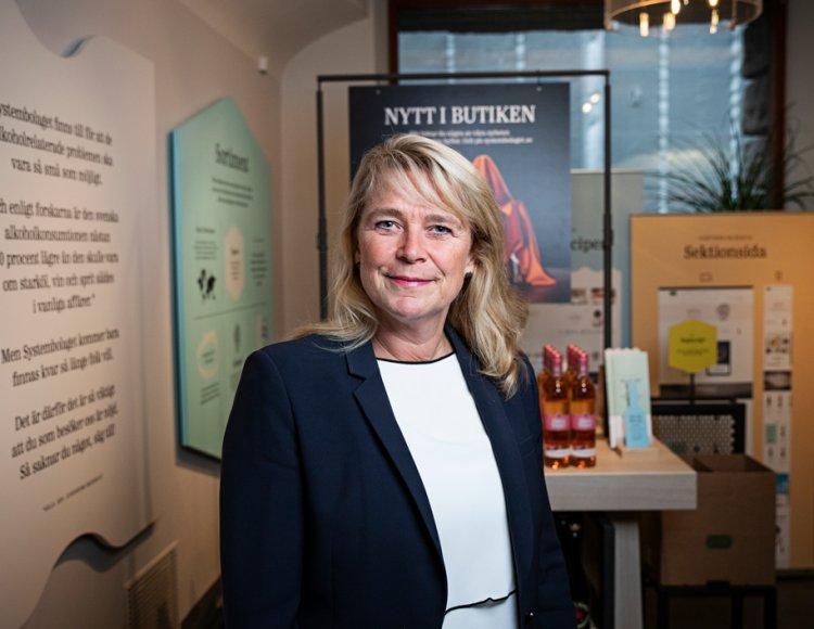 Magdalena Gerger, vd på Systembolaget, står i Systembolagets kontorslokaler med butiksmaterial i bakgrunden.