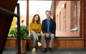 Elisabeth Eliasson och Magnus Andren sitter på en fönsterbänk i en trappuppgång.