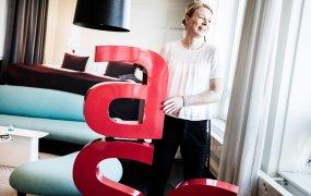 Anne EK står inomhus i ett av Scandics hotellrum och tittar ut mot fönstret. På golvet ser man stora röda bokstäver, som tillsammans bildar Scandics logotyp. A:et är staplat ovanpå s:et och Anne håller i det.