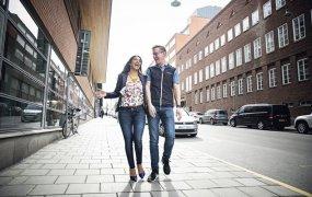 Carolina & Johan går skrattandes ute på gatan. I bakgrunden syns äldre tegelhus och parkerade bilar.