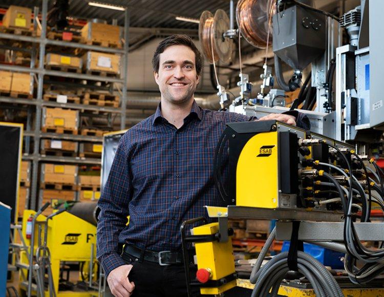 Jan Zachrisson stående bredvid ESABs arbetsmaskin inne på produktionslagret