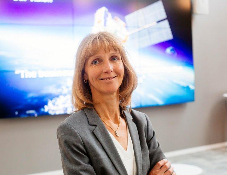 Mikaela Näslund står på Mycronics kontor med en tv-skärm i bakgrunden.