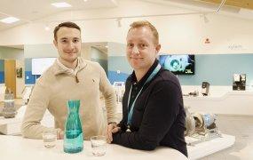 Robert Arvefalk (t.hö) och Benjamin Hasanbegovic (t.vä) står i Xylems visningslokaler med två vattenglas och en karaff framför sig.