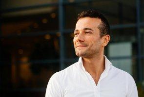 Farzad Feroz står utomhus iklädd vit skjorta och tittar mot solljuset.