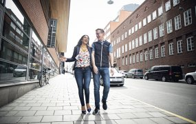 Carolina och Johan går skrattandes på gatan mellan två tegelbyggnader.