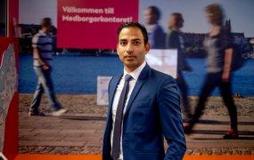 Robin Rahman, utvecklingschef, står framför en vägg som föreställer ett foto och en text: Välkommen till Medborgarkontoret! Han tittar in i kameran.