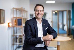 Marc Hoffmann står iklädd kostym och lutar sig mot ett ståbord på ett av E.ONs kontor.