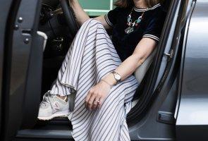 Emelie Emanuelsson, Volvo. Emelie sitter i en bil med förardörren öppen och tittar in i kameran. Ena handen har hon på ratten.