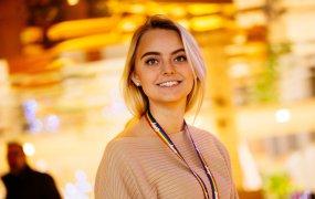 Rebecca Kullenius står i ett rum med guldfärgade lampor i bakgrunden.
