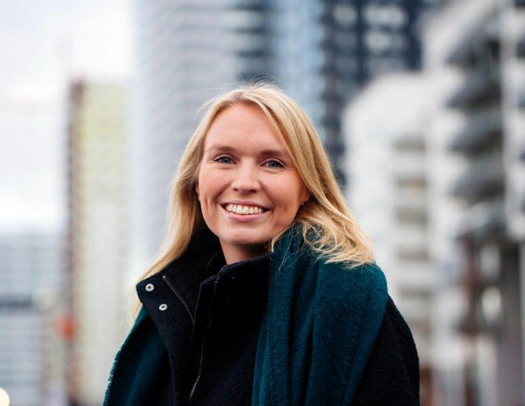 Emma Grönlund står framför utomhus med byggnader i bakgrunden.