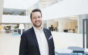 Richard Orgård, HR- och hållbarhetschef står i ett ljust och öppet kontorslandskap och ler mot kameran.