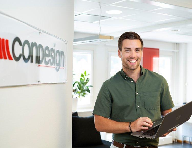 Tobias Elgström står på ett kontor, framför Condesign-logon med en dator i handen.