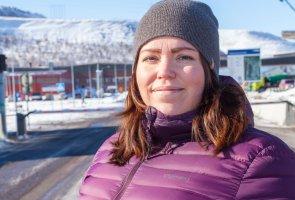 Lisa Rapp står utomhus i ett soligt Kiruna med hus och fjäll i bakgrunden.