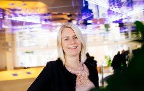 Linda Klamer, projektledare och RPA-utvecklare på EVRY, står på ett kontor och ler mot kameran. Bakgrunden är suddig och taket gnistrar lite i en lila ton.