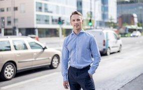 Maciej Zakrewski ståendes utepå gatan klädd i blå skjorta och mörka långbyxor. I bakgrunden skymtar en fasad och passerande bilar.