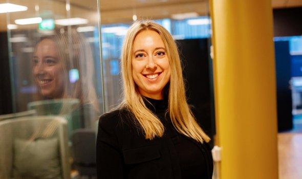 Sara Larsson står i mot en glasvägg i en korridor.