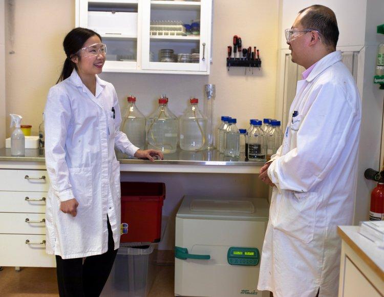 Mai Bui står i ett labb tillsammans med en kollega.