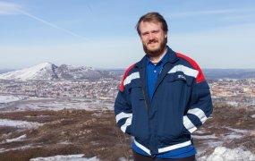 Petter Madsen står utomhus i med en gruva i bakgrunden.