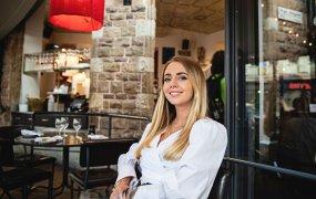 Veronica Hällblad på Svenska Brasserier sitter i restaurangmiljö och ler in i kameran.