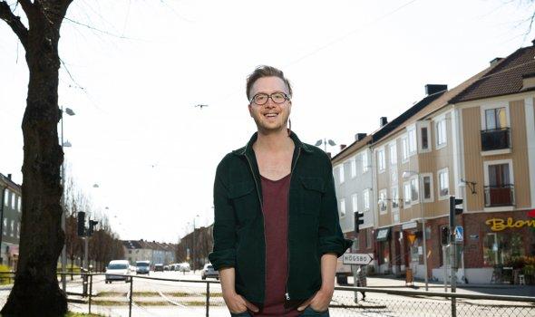 Mattias Jägerskog står utomhus med träd och lägenhetshus i bakgrunden.