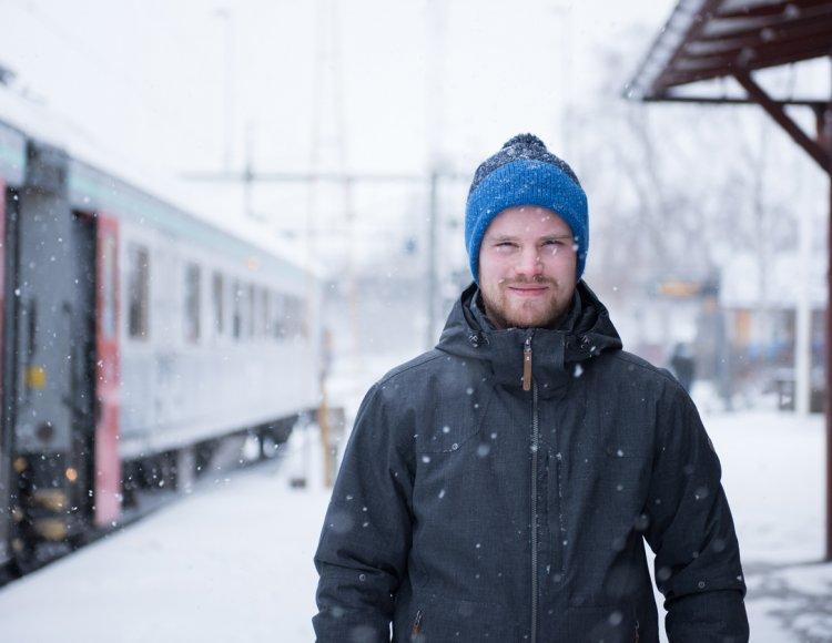 Johannes Nilsson står på en tågstation med varma ytterkläder och snö som faller.