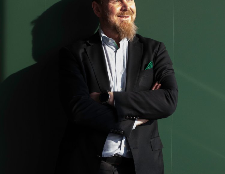 Thomas Holmberg står i solljus framför en grön vägg.