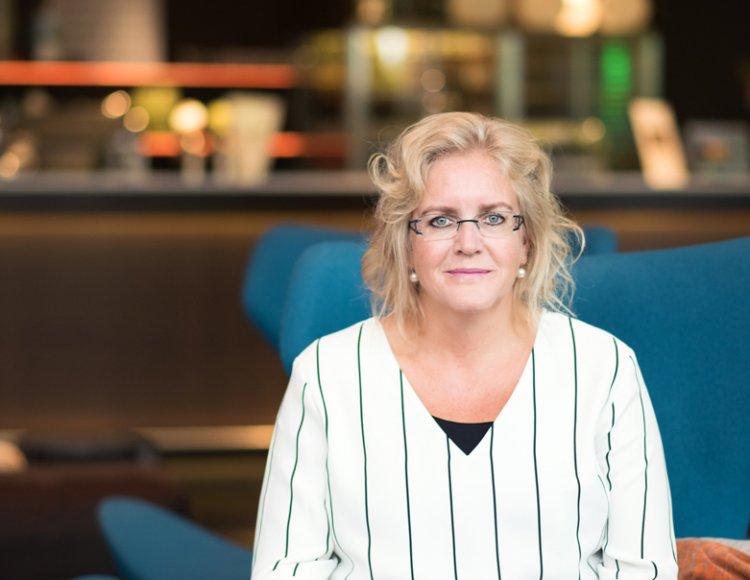 Åse Juhlin sitter i en blå fåtölj med en kaffekopp i handen med en cafédisk i bakgrunden.