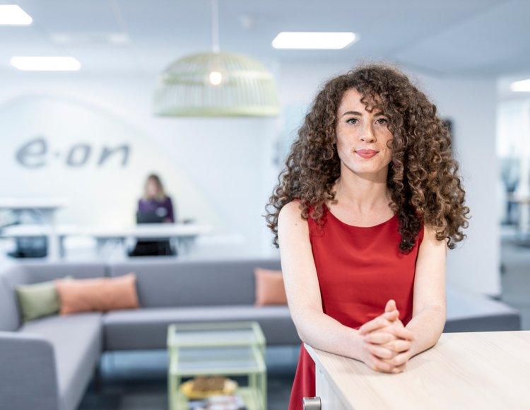 Sara Hammoura står vid ett ståbord i ett personalrum med E.ON-loggan på bäggen bakom sig.