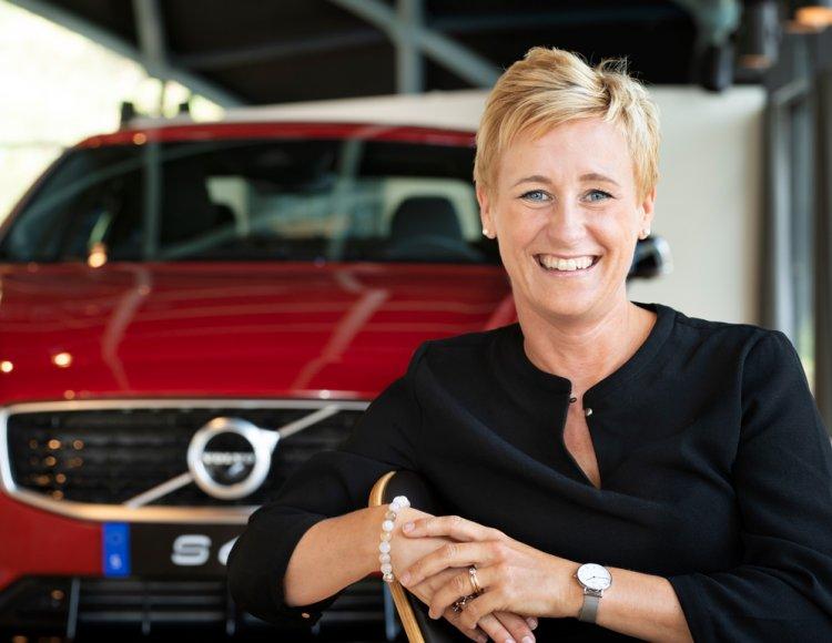 Malin Perlander Molén, Director Global Employer Branding sitter på en stol i Volvos Showroom framför en röd splitterny Volvo.