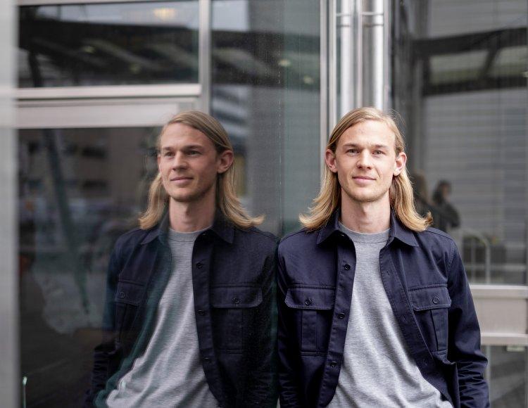 Manne Jildenbäck står utomhus, lutad mot en glasfasad i vilken han speglas. Han tittar in i kameran och ser positiv ut.