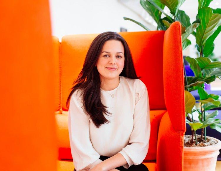 Linda Ruus, Business Controller Assistant, sitter i en orange tygsoffa med hög rygg på Marginalen Bank. Bakom henne syns en stor fiolfokus och blå dagbäddar.