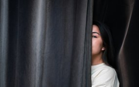 En bild med en tjej som står halvt gömd bakom en svart gardin.