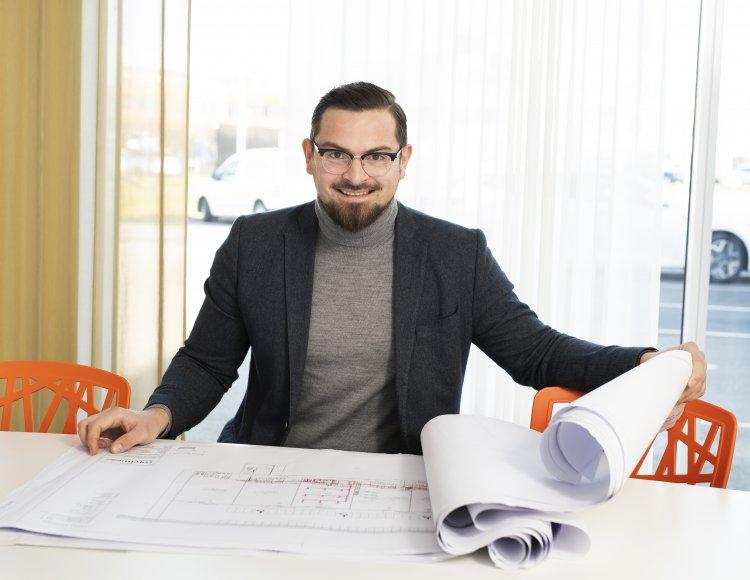 Amer Hadic, Bravida sitter vid bordet med ritningar