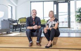 Malmö 180815 Patrick Lindqvist och Jessica Svantesson på Ikano Bank sitter i en trappa i en ljus kontorsbyggnad och ler mot kameran. I bakgrunden skymtar en soffgrupp. Foto: André de Loisted