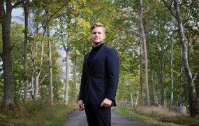 Simon Thune står, iklädd kostym, på en väg kantad av grönskande träd.
