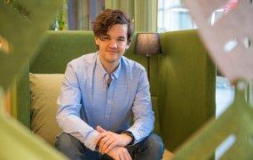 Emil Torp sitter i en grön fåtölj med hög rygg på Trafikverket. Han ler mot kameran.