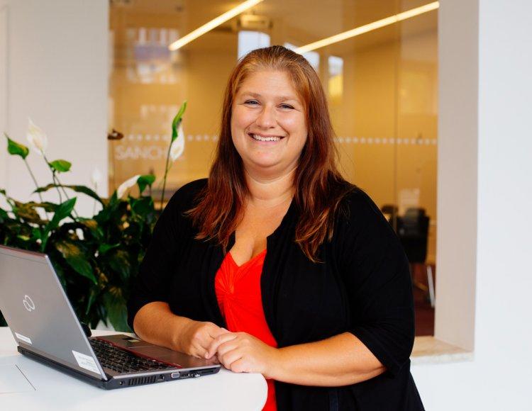 Sofia Johansson, kommunikatör på försäkringsbolaget Folksam står i den öppna konferenslokalen framför ett podium med en bärbar dator.
