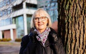 Lena Erixon står utomhus och lutar sig mot ett träd.