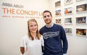 André More och Emelie Öhrn ståendes tillsammans på Assa abloys ljusa kontor. I bakgrunden sitter inramade bilder på väggarna samt företagets slogan.
