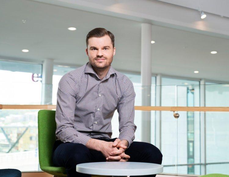Maskinprojektledaren Simon Tallnäs Winther sitter på en grön stol vid ett litet bord i Essitys ljusa lokaler. Han tittar in i kameran och ser tillfreds ut.
