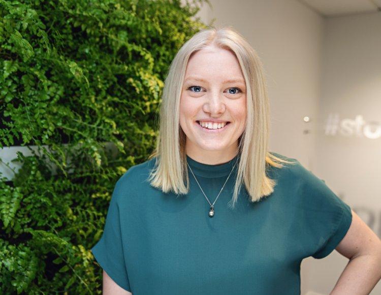 Ebba Mannheimer står inne på Stora Ensos kontor. Bakom henne syns en vägg som är helt täckt av ormbunke. Hon ler stort mot kameran.