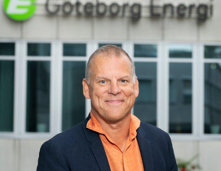 Arto Pitkaniemi står utomhus, iklädd kostym, framför Göteborg Energis lokaler med loggan ovanför.