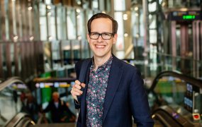 Emil Adén, Head of Employer Branding på Trafikverket står framför tunnelbaneuppgången vid centralstationen i Stockholm klädd i kavaj och mönstrad skjorta.