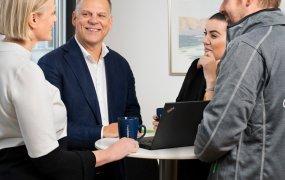 Arto Pitkaniemi står vid ett runt ståbord tillsammans med tre kollegor och pratar.