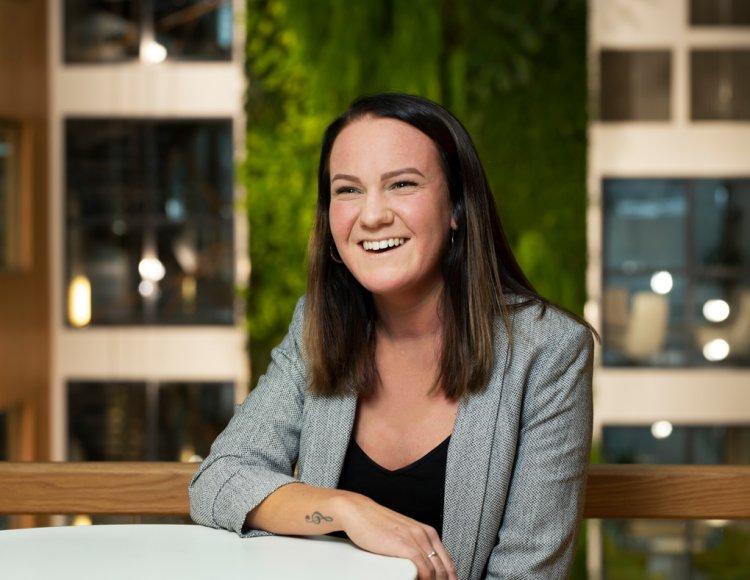 Amanda Hult sitter vid ett bord i Göteborgs Energis lokaler med en inomhusfönster och gröna växter i bakgrunden.