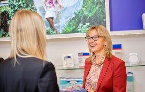 Anna Sävinger Åslund, personaldirektör Essity, står och samtalar med en kollega. I bild ser man Essitys produkter som exempelvis Tena.